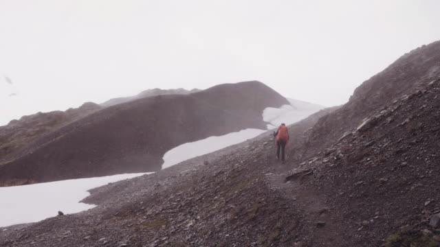 UHD 4K: Ethnic female backpacker exploring and hiking up a glacier