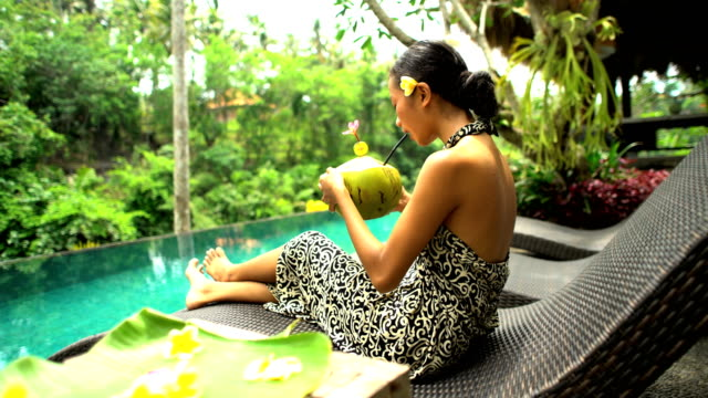 Ethnic female in sarong by infinity pool Bali