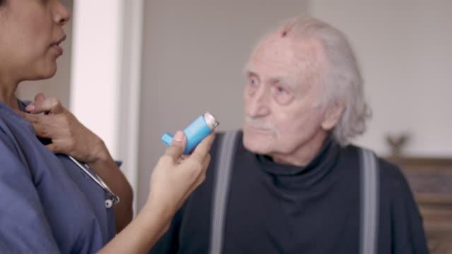 vidéos et rushes de infirmière femelle ethnique aidant le patient à la maison - inhalateur