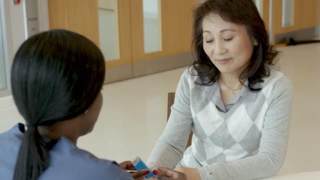 vídeos de stock e filmes b-roll de ethnic female nurse helping patient with asthma - asmático