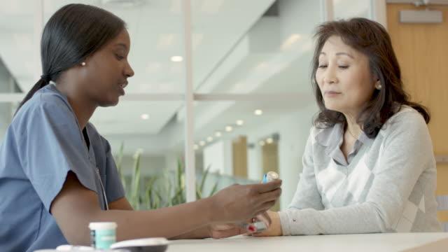vidéos et rushes de infirmière femelle ethnique aidant le patient avec l'asthme - inhalateur