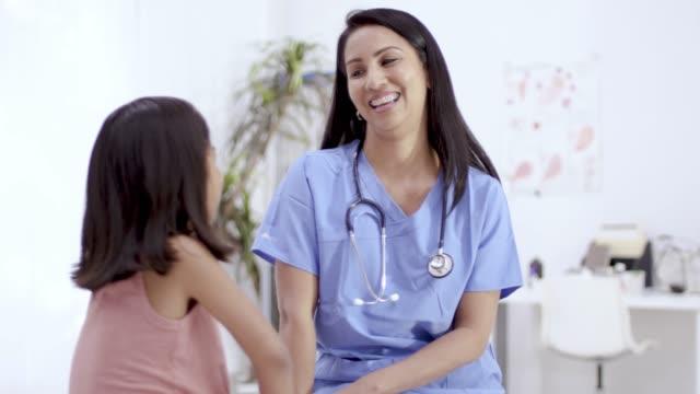 vídeos de stock, filmes e b-roll de doutor pediatra fêmea étnico com paciente da criança - enfermeira pediátrica