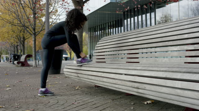 vídeos y material grabado en eventos de stock de étnica mujer atar sus zapatos antes de una carrera - corredora de footing
