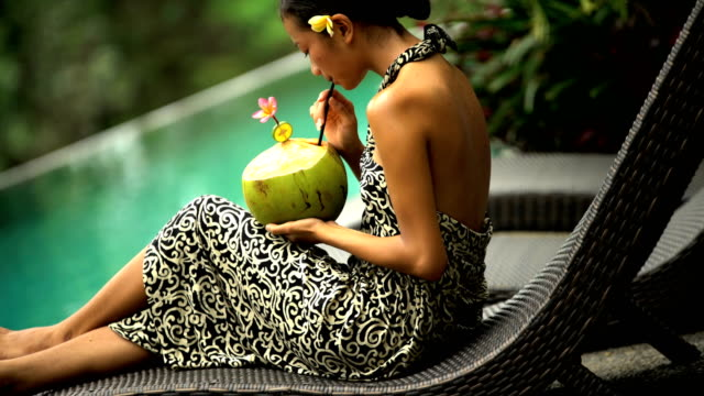 ethnic girl relaxing by tropical jungle pool bali - infinity pool stock videos & royalty-free footage