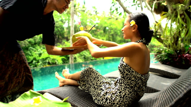 Ethnic girl relaxing by tropical jungle pool Bali