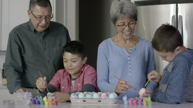 Ethnic Grandparents Painting Easter Eggs with Their Two Young Grandsons