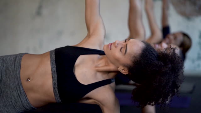 ethnic group of young adult females doing planks and core exercises - yoga studio stock videos & royalty-free footage