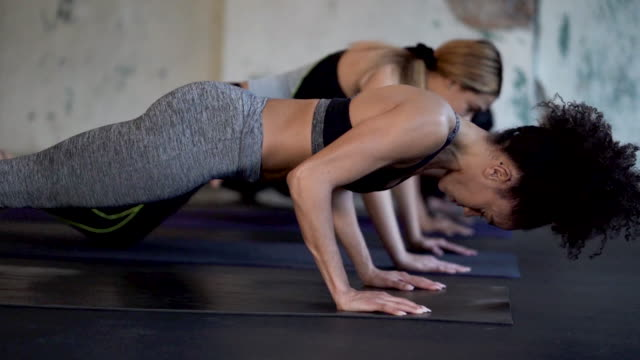 ethnic group of young adult females doing planks and core exercises - physical stance stock videos & royalty-free footage