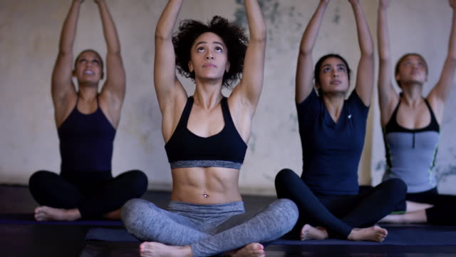 ethnic group of young adult females group doing yoga in a fitness studio - fatcamera stock videos & royalty-free footage