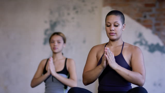 ethnic group of young adult females group doing yoga in a fitness studio - yoga studio stock videos & royalty-free footage