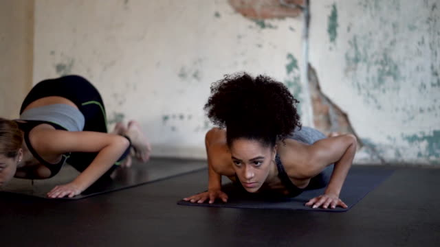 ethnische gruppe von jungen erwachsenen weibchen-gruppe beim yoga im fitnessstudio - yogastudio stock-videos und b-roll-filmmaterial