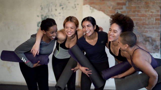 Ethnic group of young adult females posing and laughing together after yoga class inside a fitness studio