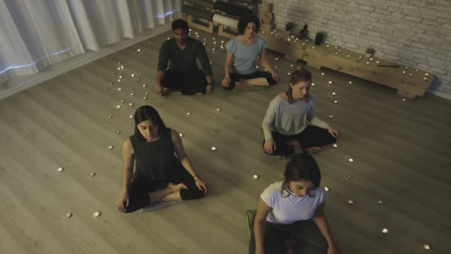 ethnic group of young adults meditating together - zen like stock videos & royalty-free footage