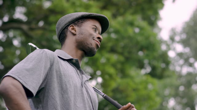 ethnic male golfer talking while holding golf club - golfer stock videos & royalty-free footage