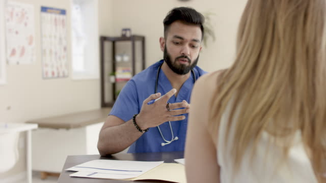 ethnic male nurse doing medical checkup with female patient - fatcamera stock videos and b-roll footage