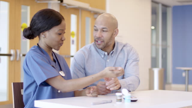 ethnic male patient with diabetes being helped by nurse - diabetes stock videos & royalty-free footage