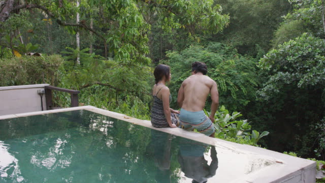 ethnic man sitting next to his girlfriend at the edge of a pool - honeymoon stock videos & royalty-free footage