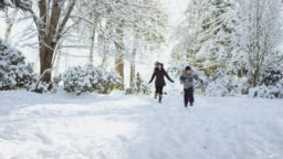 Ethnic Mother and Her Sons Running in the Snow