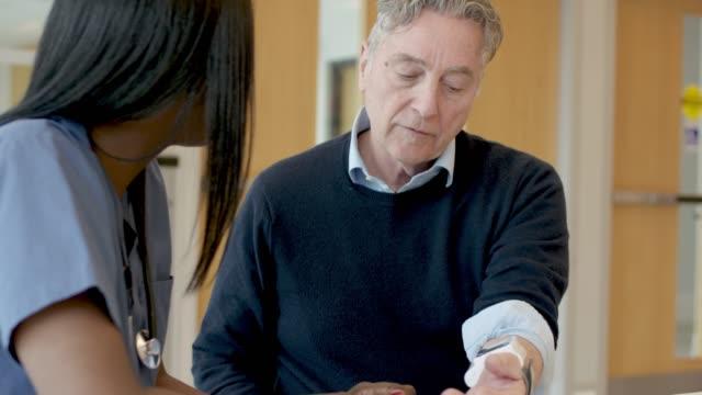 vídeos y material grabado en eventos de stock de enfermera étnica tomando la presión arterial de sus pacientes mayores - colesterol