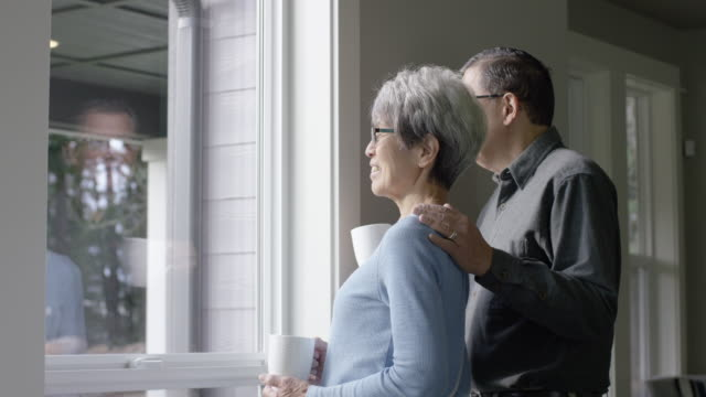 Ethnic Senior Couple Looking Out Window While Holding Mugs