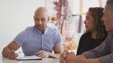 vidéos et rushes de couple senior ethnique avec conseiller financier - métier de la vente