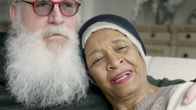 vídeos de stock, filmes e b-roll de a fêmea sênior étnica com cancro relaxa com seu marido caucasiano - radioterapia