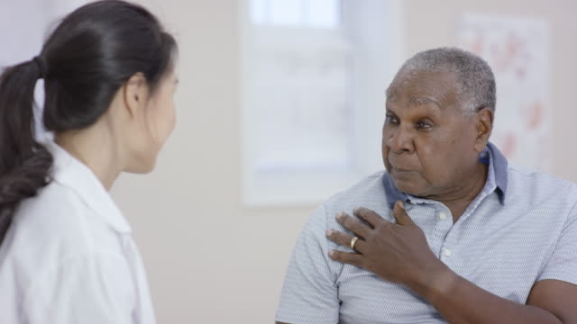 vídeos de stock e filmes b-roll de ethnic senior man talking to a female doctor during an appointment - diabetes