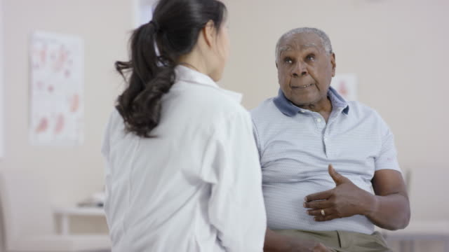 ethnic senior man talking to a female doctor during an appointment - coat garment stock videos & royalty-free footage