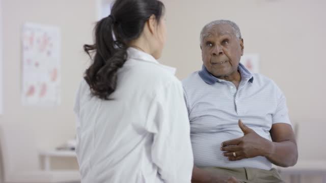 vidéos et rushes de ethnique homme senior, parler à une femme médecin lors d'un rendez-vous - manteau et veste