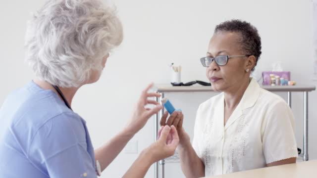 シニア看護師との健康診断を受けたエスニックシニア患者 - 喘息点の映像素材/bロール