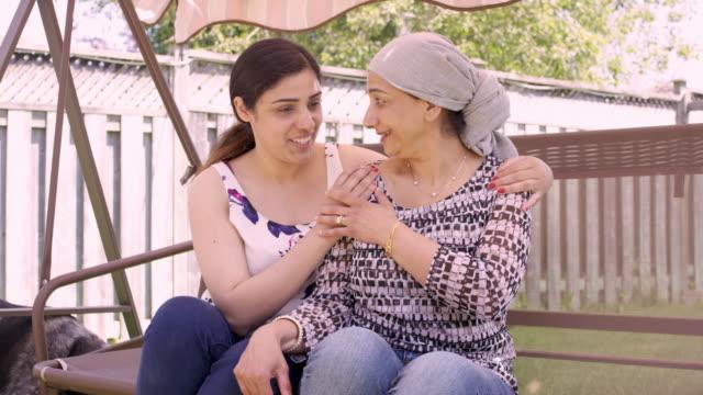 vídeos de stock, filmes e b-roll de mulher sênior étnica com tempo da despesa do cancro com crianças adultas - radioterapia