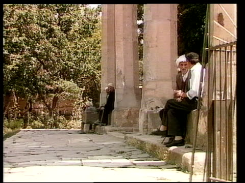 ethnic unrest; itn lib yugoslavia: kosovo: ext people along street towards side 2 men seated between pillars on steps of building chatting as another... - politik stock-videos und b-roll-filmmaterial