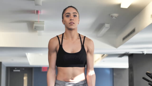ethnic young adult female doing bicep curls at the gym with weights - bicep stock videos & royalty-free footage
