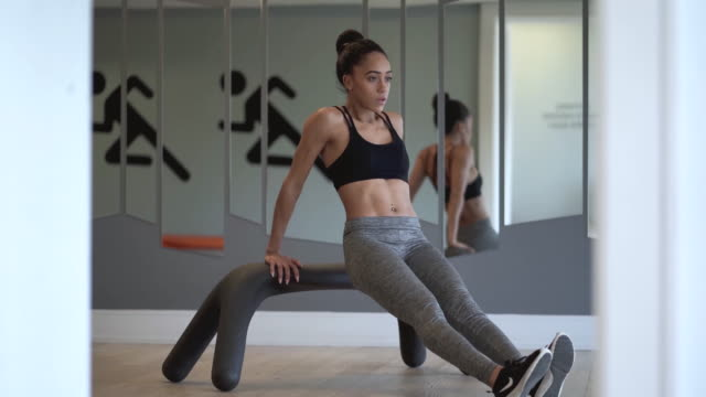 ethnic young adult female doing tricep dips at the gym in a fitness studio - bicep stock videos and b-roll footage