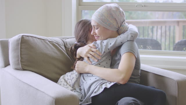 Ethnic Young Adult Female with Cancer Holding a Young Girl