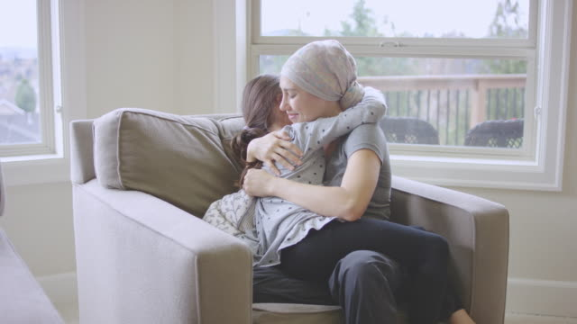 vídeos de stock e filmes b-roll de ethnic young adult female with cancer hugging her daughter - careca