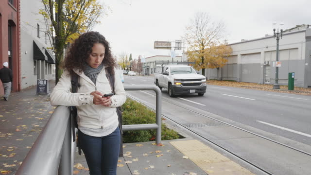 ethnic young female adult waits for streetcar - bus stop stock videos & royalty-free footage