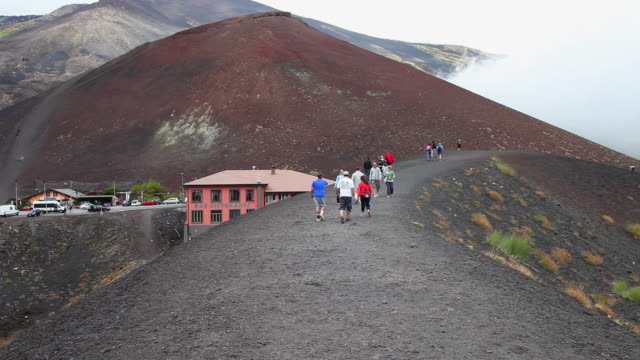 Etna mountain, tourists walking around a crater