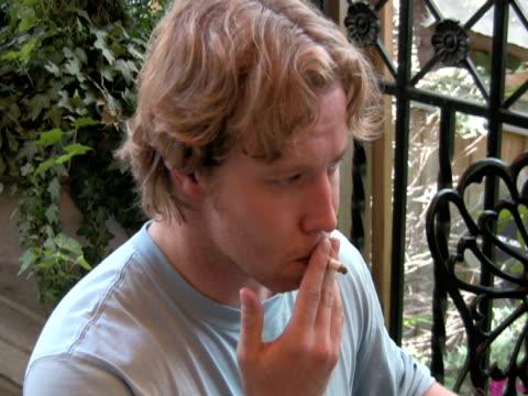 燻製器など、五感に吸い込み、息を吐いたとき、同時に - 若い男性だけ点の映像素材/bロール