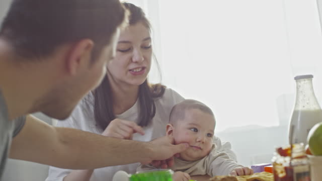 eurasian couple with baby boy eating breakfast - frühstück stock-videos und b-roll-filmmaterial