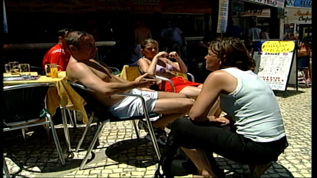 England fans clash with police in Albufeira ITN PORTUGAL Albufeira EXT MS tattooed England fans sitting at cafe table MS England fan sat at table...