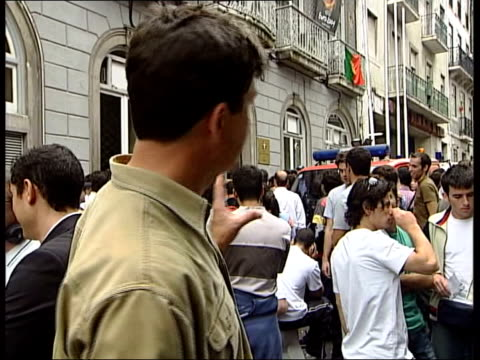 fans hunt for england v portugal tickets:; itn portugal: lisbon: ext/night gv people queuing outside portugese football association for tickets to... - ticket stock videos & royalty-free footage