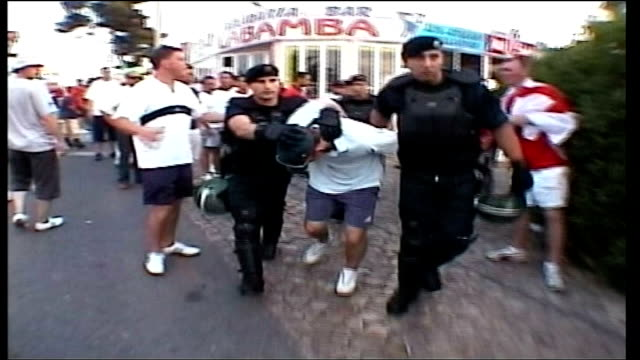 hooligans arrive home itn portugal albufeira ext gv group of english fans celebrating england's win against switzerland gv english man taken away by... - hooligan stock videos & royalty-free footage