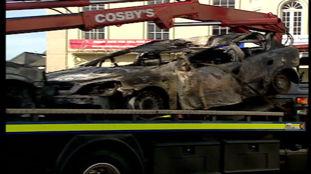 hooligans riot after france defeat england 21 itn england london croydon ext burnt out remains of cars on tow truck london england fans leaving bar... - rimorchiare video stock e b–roll