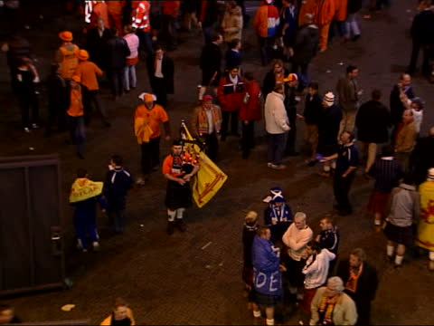 wales v russia/holland v scotland; itn netherlands: amsterdam: ext/night i/c tms scotland fan playing bagpipes pull out - playoffs stock videos & royalty-free footage