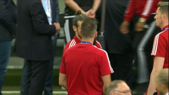 welsh prepare for match against russia; france: toulouse: ext welsh footballers towards onto pitch players along on pitch gareth bale chatting to... - typisch walisisch stock-videos und b-roll-filmmaterial