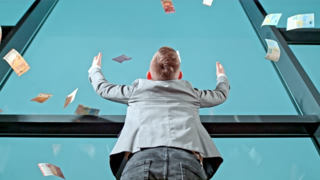 Euro banknote falling over young businessman boy at office window, super slow motion