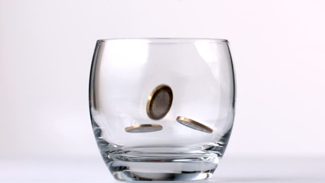 euro coins falling in a glass - money makes the world go around stock videos and b-roll footage