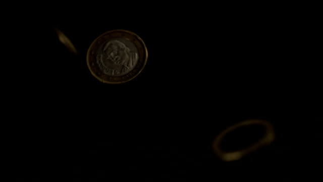 euro coins falling on black surface - money makes the world go around stock videos and b-roll footage
