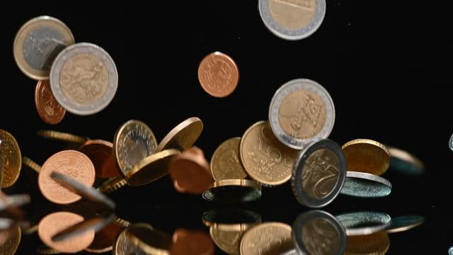 vídeos de stock, filmes e b-roll de slo mo ld euro moedas caindo sobre uma superfície negra - variation